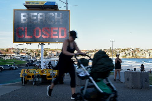 A woman with baby pushchair walks past a 'beach closed' sign.
