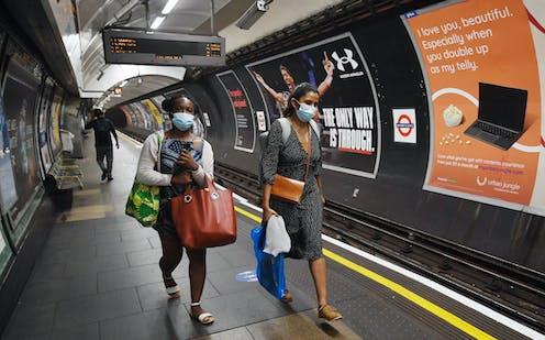 Two women wearing face masks on London Underground