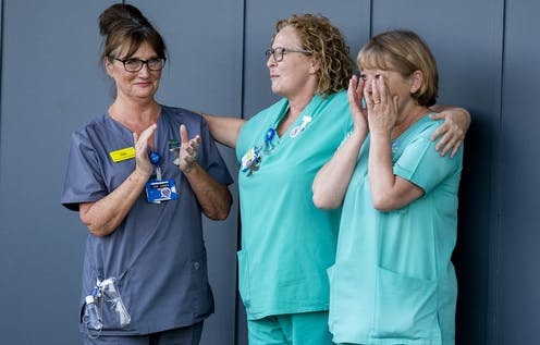 Three women healthcare professionals outside an NHS hospital