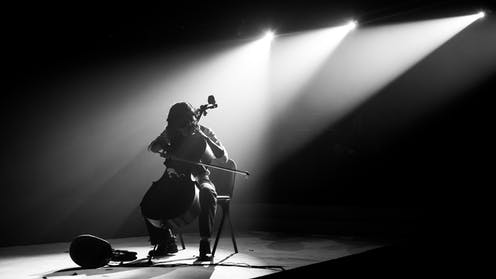 A cello player alone on stage, silhouetted by spotlights.