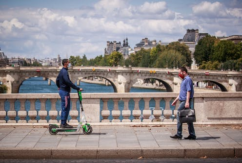 A man with a briefcase and a man on an electric scooter cross a bridge over the Seine, Paris, in opposite directions.