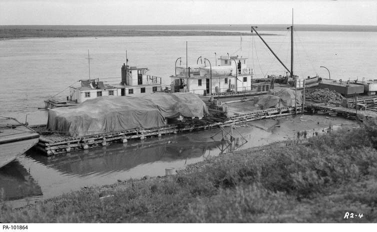 A vintage black-and-white photograph of a wharf with two shipping vessels docked.