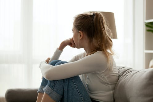 A woman sitting on a sofa looking out of the window.