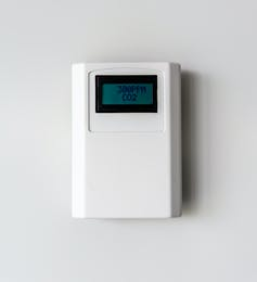 A carbon dioxide meter mounted on a white wall showing a reading of 300 parts per million.