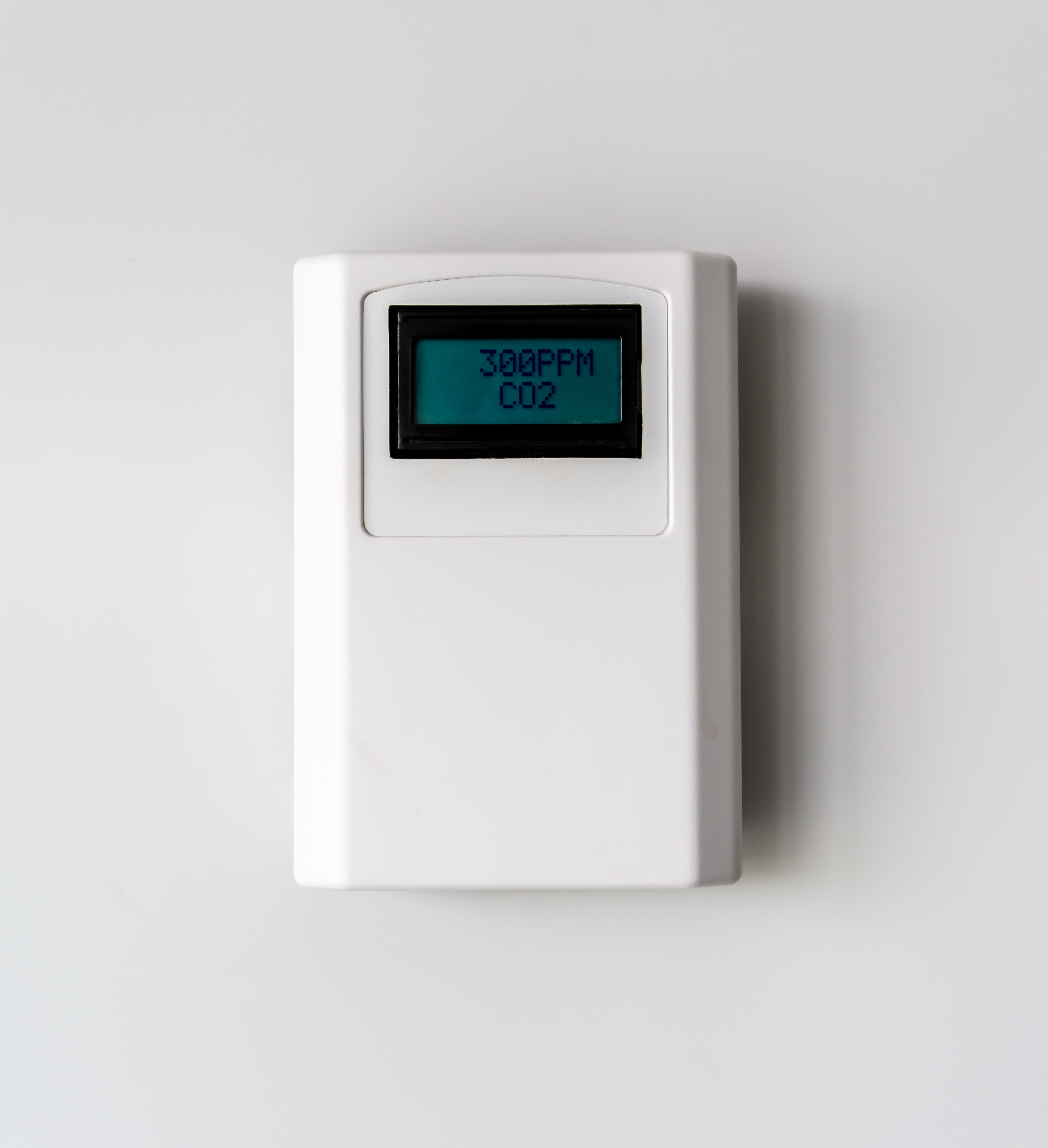 A carbon dioxide meter on a white wall shows a reading of 300 ppm.