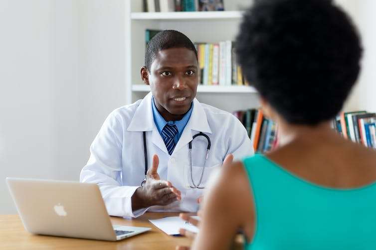 A doctor is seated at a table talking to a patient.