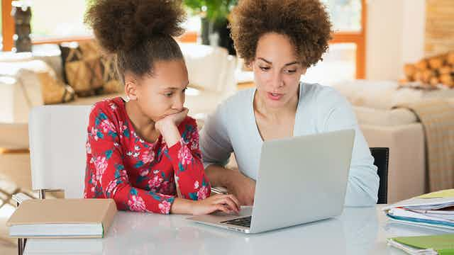 stock photo of mother and daughter looking at a laptop