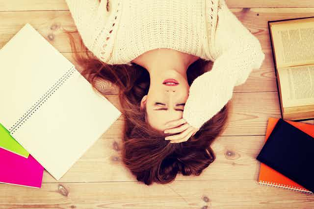 Girl lying on her back with her hand on her forehead, books lying open around her