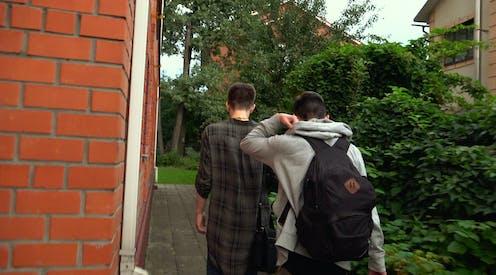 Two boys walk along side of house