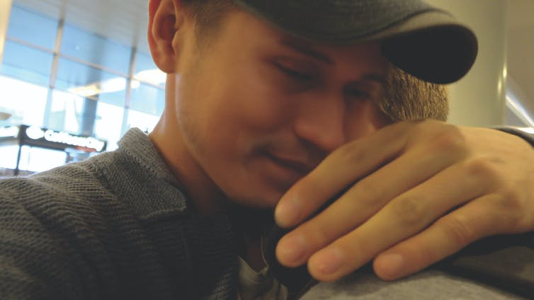 Two men embrace at airport