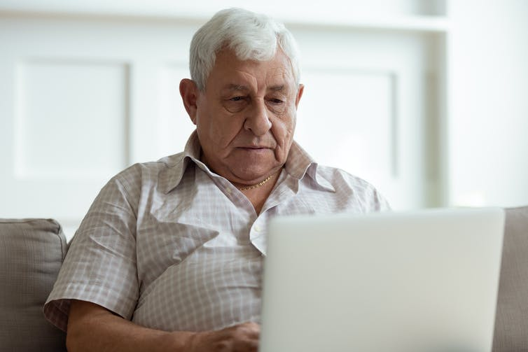 A man looks at a laptop computer screen.