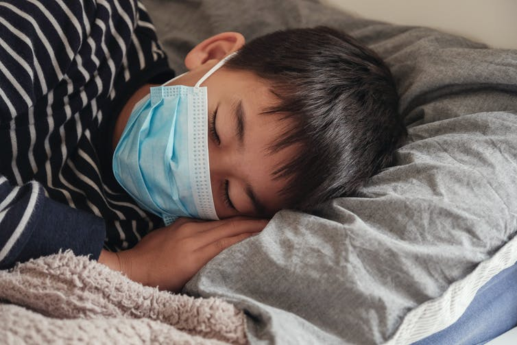 Boy wearing surgical mask is sleeping on grey pillow.