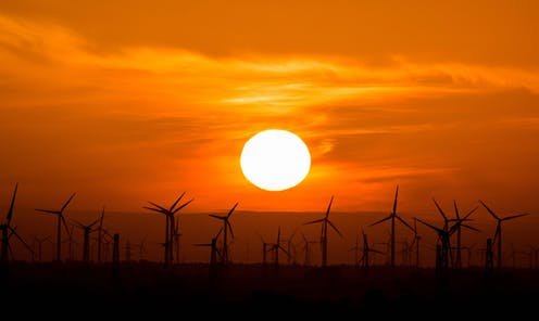 Hundreds of wind turbines along the horizon, under a setting sun.