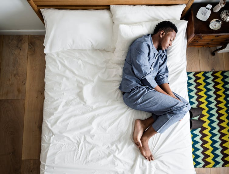 Man lying in bed looking lonely