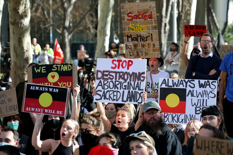 A group of protesters holding signs that read 'stop destroying Aboriginal sacred lands'.