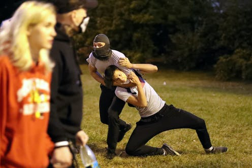 A man in a balaclava holds another in a headlock during protests in Belarus.