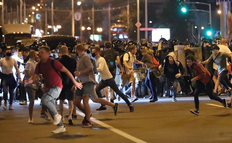 Protestors running from riot police.