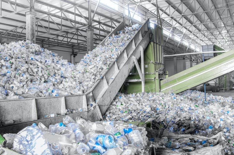 A pile of plastic bottles being processed at a factory.
