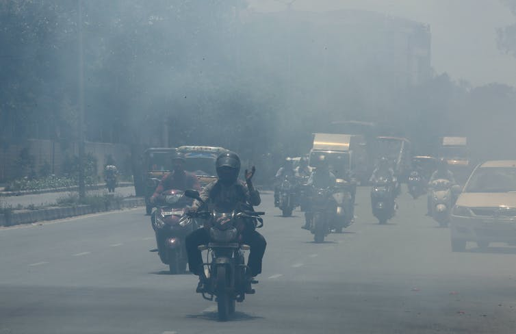 A road in Bangalore crowded with motorcycles and cars under a thick haze.