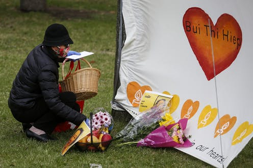 A woman wearning a mask lays flowers at makeshift memorial for a dead Cargill worker.