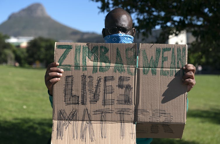 Protestor holds up sign: Zimbabwean Lives Matter