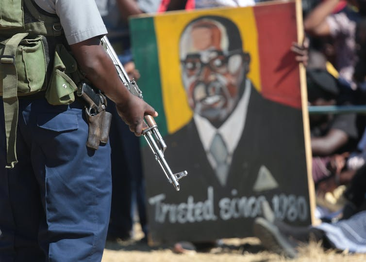 Armed guard in front of a Robert Mugabe poster.