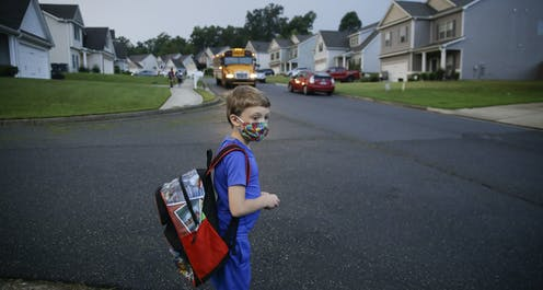 A young boy in a face mask and carrying a backpack looks tentative as he waits by a road in a subdivision as his school bus approaches.