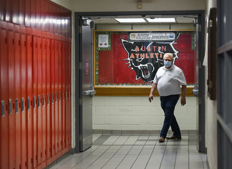 Doug Ford, wearing a mask, walks down a school hallway with a row of red lockers to the left.