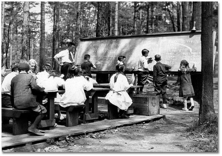 Students sit at desks outdoors in front of a chalkboard.