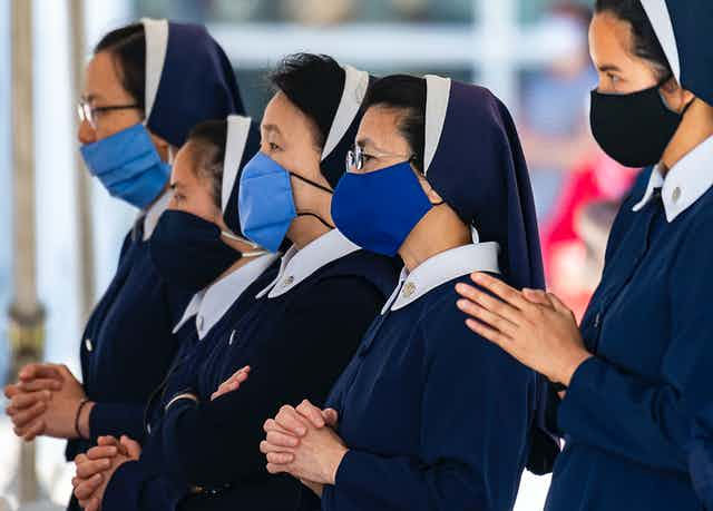 Four nuns wearing masks during a church service