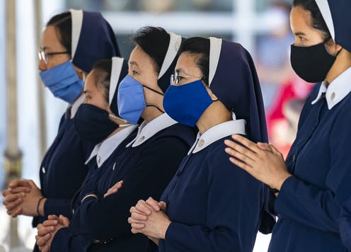 Four nuns wearing masks during a church service