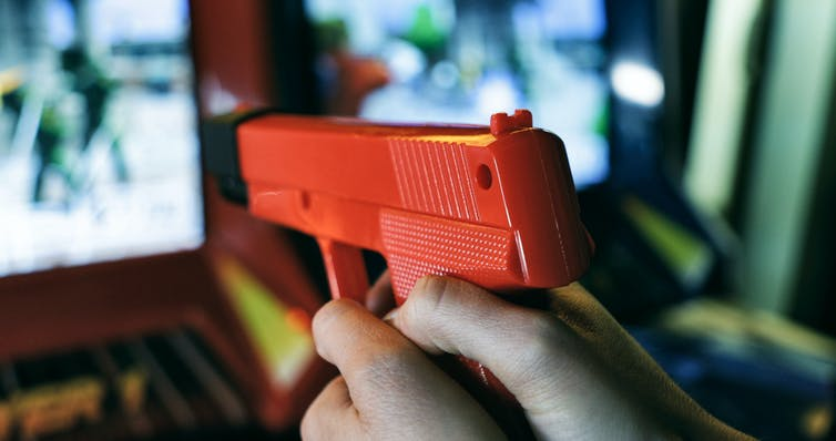 Plastic arcade game gun pointed at screen.