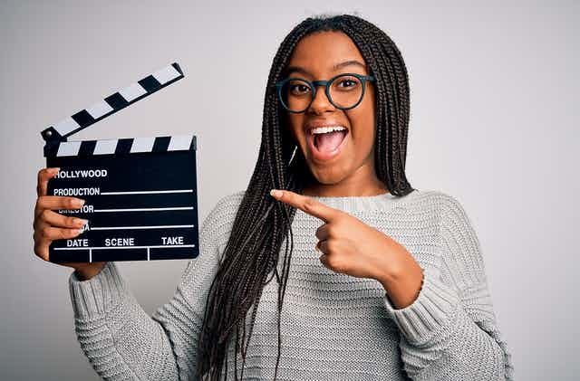Woman points to a clapperboard she's holding up.