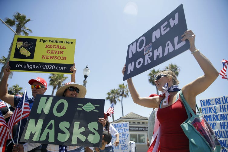 Protesters hold signs that read No Masks and No New Normal at a protest in the California sunshine.