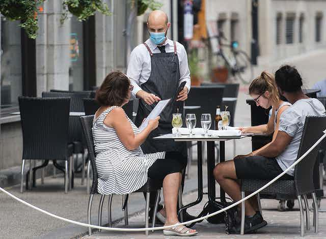 A waiter wearing a face mask takes orders from three diners on an outdoor patio.