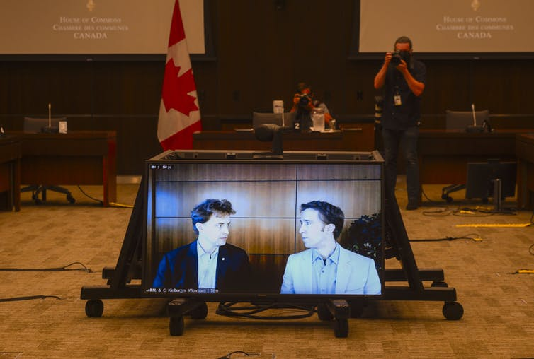 Marc Kielburger and Craig Kielburger appear on a screen in a government building.