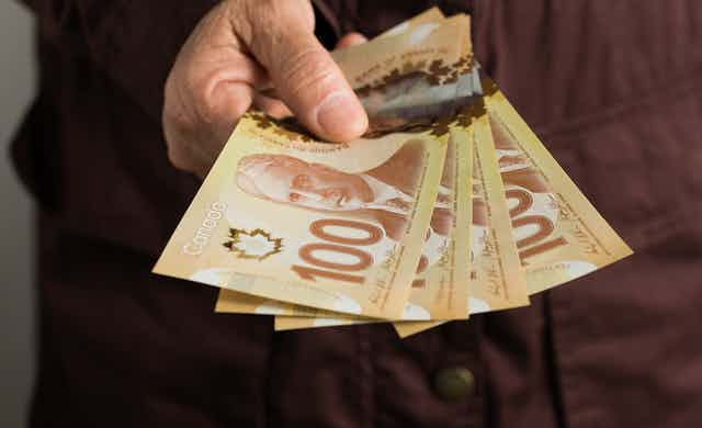A hand holds a wad of Canadian $100 bills.