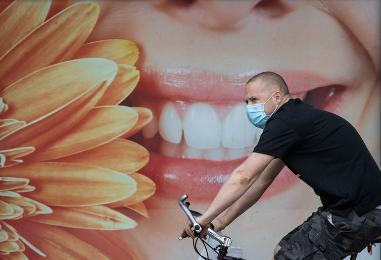 A man wearing a mask cycles past a mural featuring a smiling face in front of a dental office.