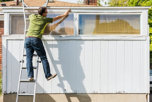 Man painting shed standing precariously on ladder.