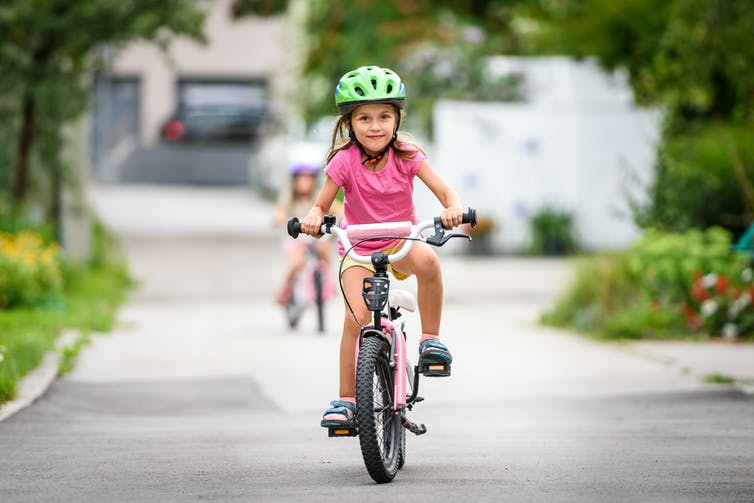 Young girl riding her bike.