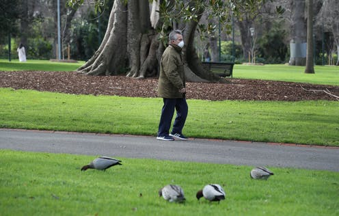 Man wearing face mask walking in park