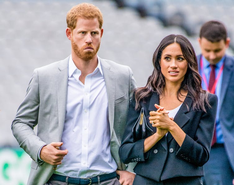 Harry and Meghan looking uncertain at public event.