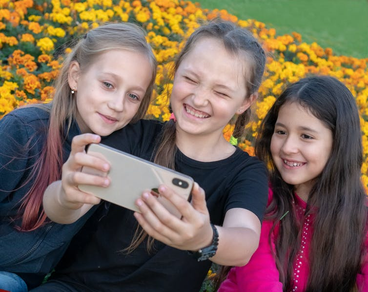 Three young girls video themselves on a smartphone.