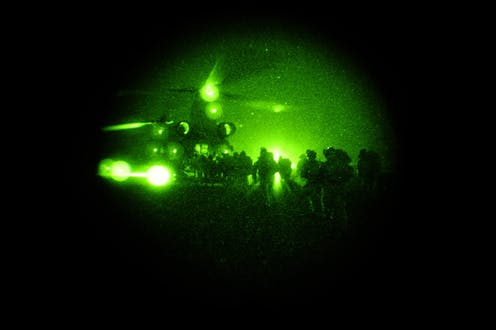 Special operations taskgroup soldiers file into a chinook under cover of darkness