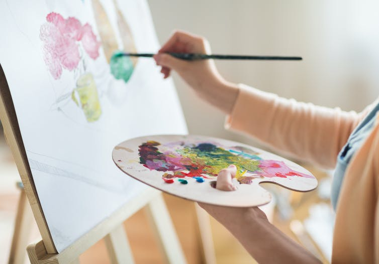 A woman painting on an easel