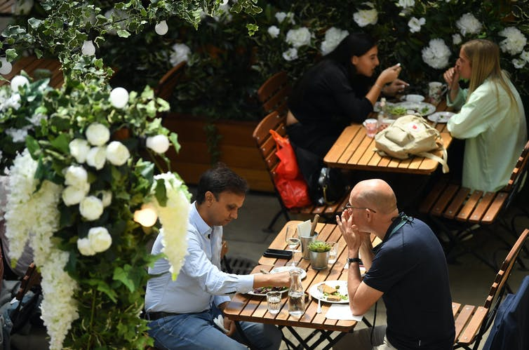 People eating outside at a restaurant at socially distanced tables.