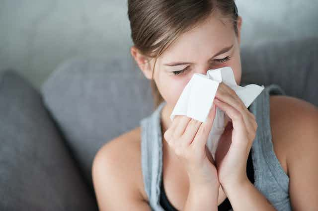 Woman with a common cold, blowing her nose