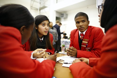 Four high school students sit around a table in discussion
