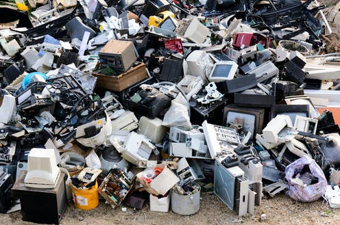 A mountain of electronic waste, including computer monitors and printers.