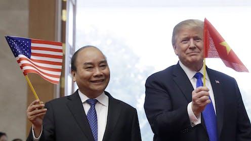 U.S. President Donald Trump waves a Vietnam flag as Vietnamese Prime Minister Nguyen Xuan Phuc waves an American flag.